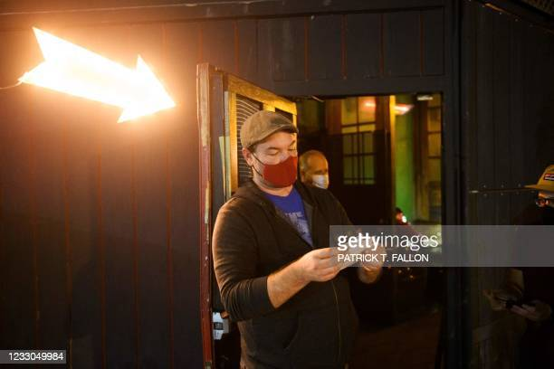 Kindrick Brooke checks a vaccination card outside Risky Business, that was once The Other Door but closed during the Covid-19 pandemic in the North...