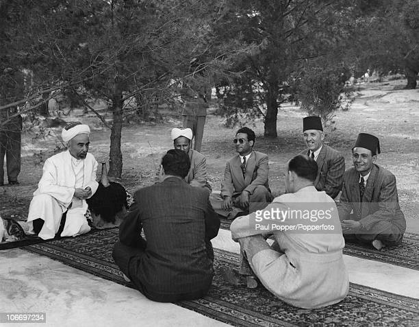 King Abdullah I of Transjordan holds a conference in the grounds of Raghadan Palace in Amman Jordan 14th June 1948 He is resting his arm on a saddle...