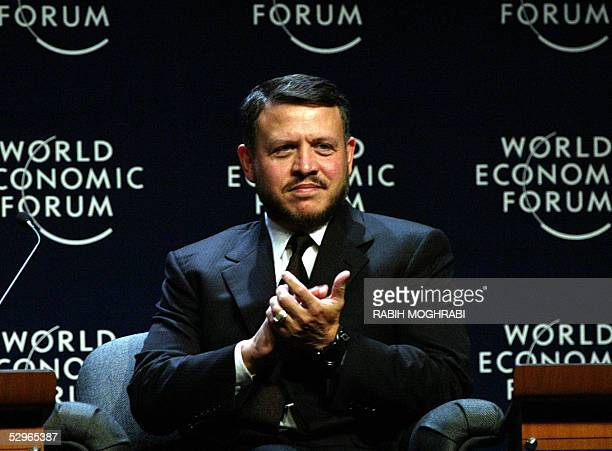 King Abdullah II of Jordan, claps at the final session of the World Economic Forum in the Jordanian Dead Sea resort of Shuneh, south of Amman, 22 May...