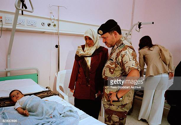 King Abdullah of Jordan photographed during a visit to a hospital in the south of the country. In the background is Queen Rania. King Abdullah bin...
