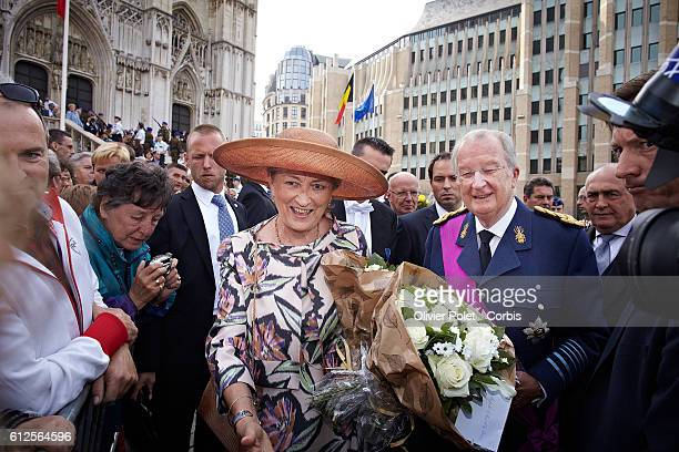 King Albert II of Belgium waves next to Queen Paola of Belgium on their way to the Te Deum mass for the King's feast at the Saint Michael and St...