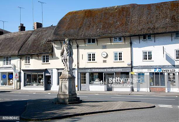 King Alfred statue in the market place and thatched shop buildings in the village of Pewsey Wiltshire England