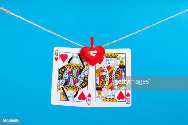 king and queen of hearts isolated with clothes peg rope over blue background - hearts playing card stock photos and pictures