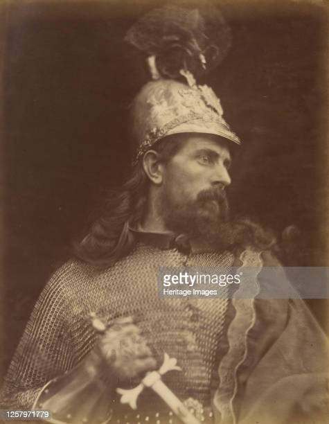 King Arthur September 1874 A photograph of the torso and head in profile of a bearded and longhaired knight with helmet and chainmail gripping a...