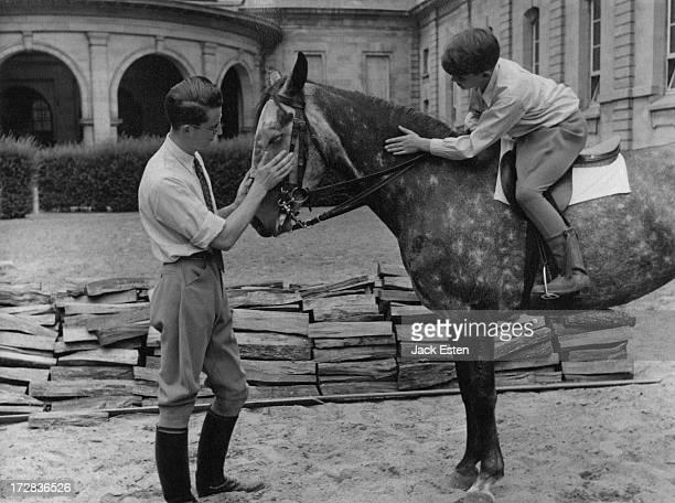 King Baudouin of Belgium and Prince Alexander of Belgium pet their Irish horse at the Royal Palace of Laeken Brussels circa 1954
