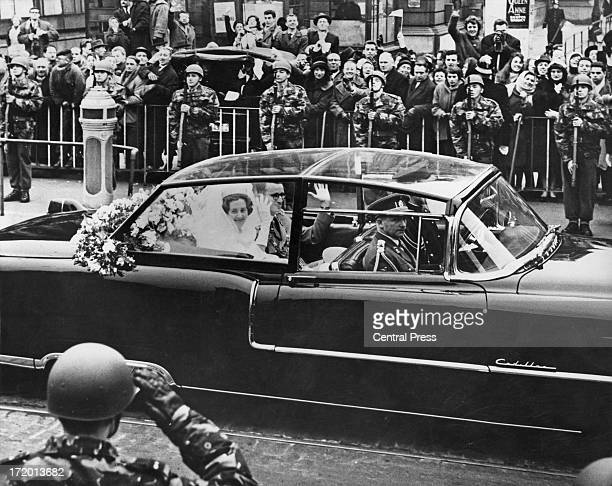 King Baudouin of Belgium and Queen Fabiola of Belgium wave to the crowds on the drive back to the Palace after their wedding service at the Cathedral...