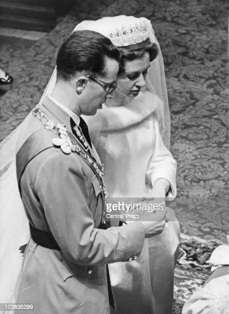 King Baudouin of Belgium places the ring on the finger of Queen Fabiola of Belgium during their wedding ceremony at the Cathedral of St Michael and...