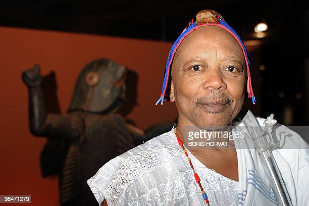 King Behanzin of Benin poses in front of a statue represented his early 19th century ancestor King Behanzin during his visit at the Quai Branly...