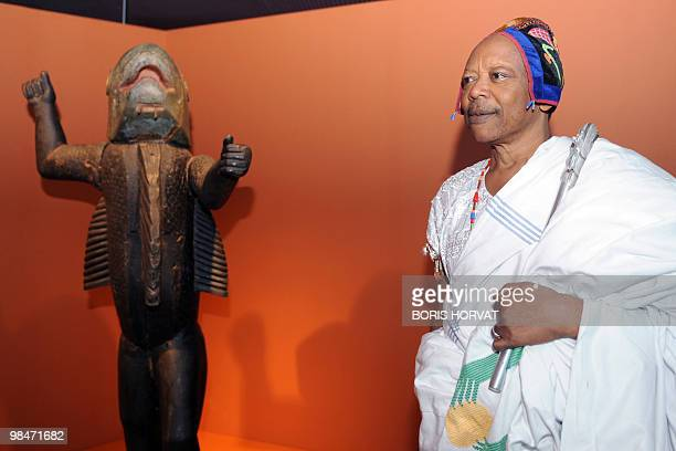 King Behanzin of Benin poses near a statue represented his early 19th century ancestor King Behanzin during his visit at the Quai Branly primitive...