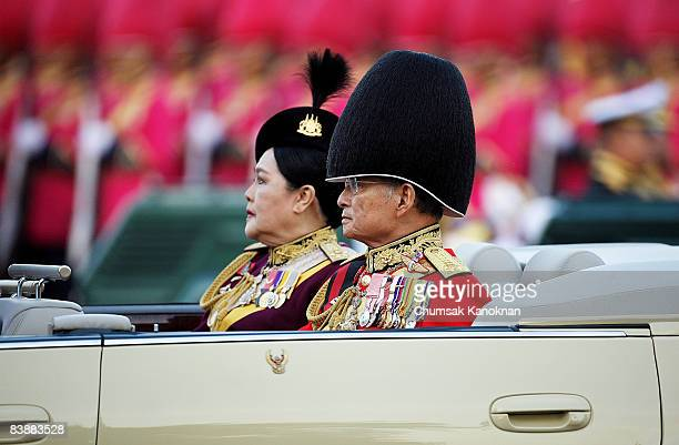King Bhumibol Adulyadej and Queen Sirikit of Thailand review the honor guard during the trooping of the colors to honor the King's 80th birthday at...