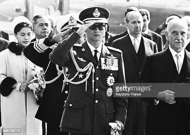King Bhumibol Adulyadej of Thailand aka Rama IX and austrian president Adolf Scharf during the national anthems in Vienna Austria Behind them Queen...