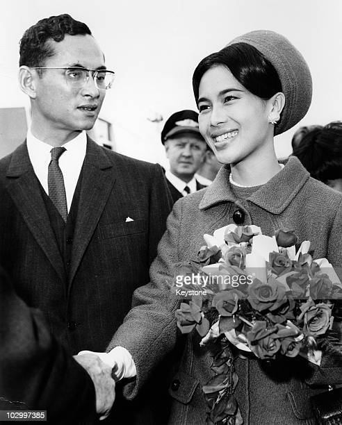 King Bhumibol Adulyadej of Thailand and Queen Sirikit of Thailand holding a bouquet of flowers as she shakes hands with an official before boarding...
