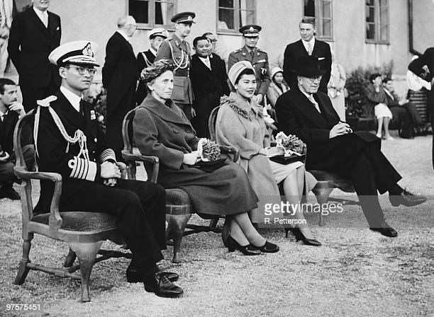 King Bhumibol and Queen Sirikit of Thailand watch a performance by Swedish folk dancers at Skansen a zoological garden in Stockholm during a state...