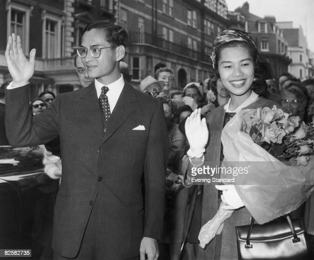 King Bhumibol and Queen Sirikit of Thailand wave to the crowds during a visit to Britain, 1960.