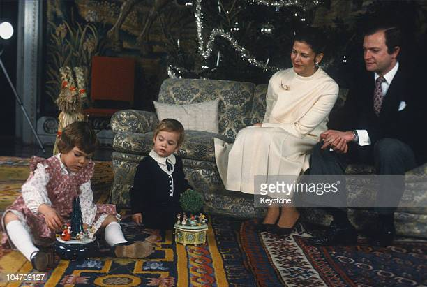 King Carl Gustaf XVI and Queen Silvia of Sweden watch their children Princess Victoria and Prince Carl Philip play with toys during Christmas 1981