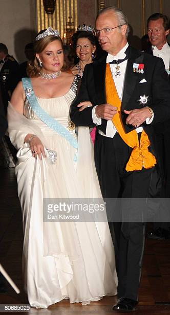 King Carl XVI Gustaf escorts Grand Duchess Maria Teresa of Luxembourg to a state banquet at the Royal Palace in Stockholm on the first day of a three...