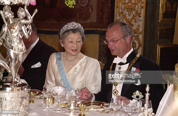 King Carl XVI Gustaf of Sweden and Empress Michiko talk during the state dinner at the Stockholm Palace on May 29 2000 in Stockholm Sweden