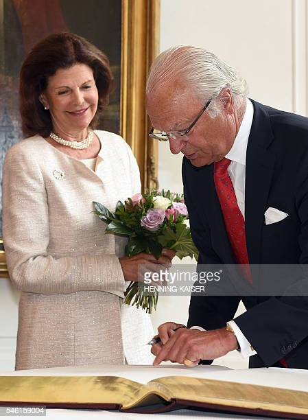 King Carl XVI Gustaf of Sweden and Queen Silvia of Sweden sign a guest book on July 11 2016 at the townhall in Aachen / AFP / dpa / Henning Kaiser /...