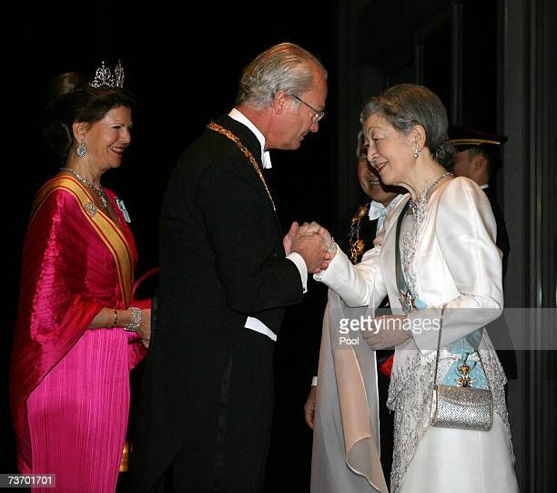 King Carl XVI Gustaf of Sweden greets Empress Michiko of Japan as Queen Silvia of Sweden and Emperor Akihito of Japan look on prior to their dinner...