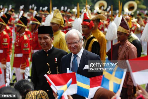 King Carl XVI Gustaf of Sweden greets Indonesian schoolchildren with Indonesia's President Joko Widodo during a welcoming ceremony at the...