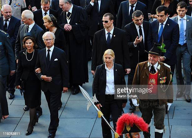 King Carl XVI Gustav of Sweden and Queen Silvia of Sweden walk in the cortege during the funeral ceremony for Otto von Habsburg seen in historic...