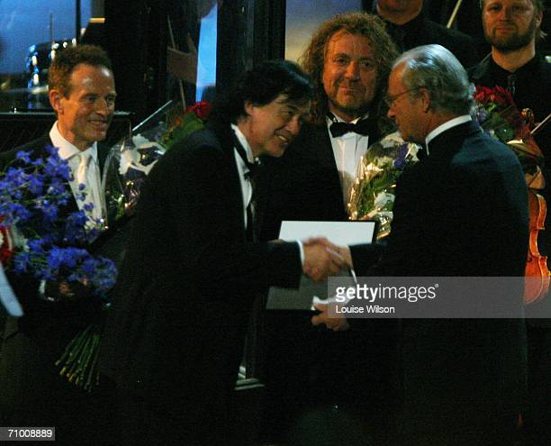 King Carl XVI Gustav presents Jimmy Page of Led Zeppelin with an award as John Paul Jones and Robert Plant of Led Zeppelin look on during the Polar...