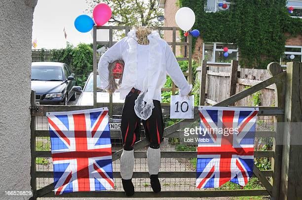 CONTENT] King Charles and head scarecrow hung on a gate with union jack flags and balloons Village Queen's jubilee celebrations