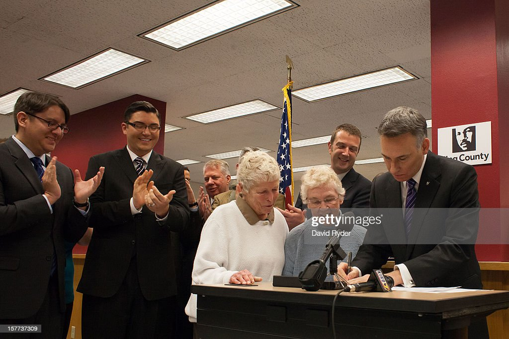 King County Executive Dow Constantine (R) signs the first same-sex marriage license in Washington state for Jane Abbott Lighty (C) and Pete-e Petersen (2nd, R) at the King County Recorder's Office on December 6, 2012 in Seattle, Washington. At left are Brendon K. Taga and Jesse Page, who were second in line. The office opened at 12:01 AM PST to begin issuing marriage licenses to same-sex couples for the first time after Washington voters chose to legalize same-sex marriage in November's election.