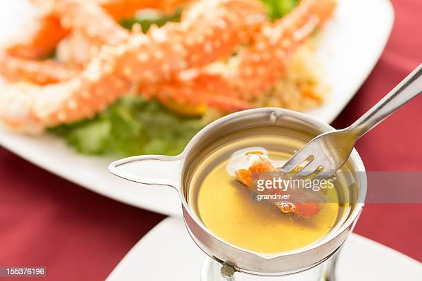 king crab dipped in butter - crab leg stock photos and pictures