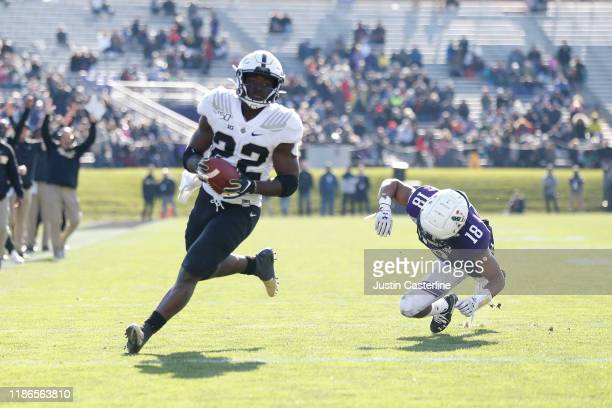 King Doerue of the Purdue Boilermakers avoids a tackle from Cameron Ruiz of the Northwestern Wildcats to score a touchdown during the second quarter...
