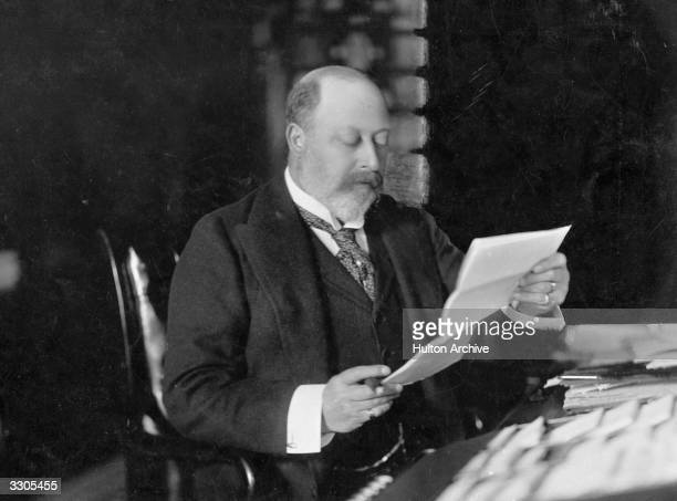 King Edward VII, , who ascended the British throne in 1901, as Prince of Wales, reading at Sandringham, Norfolk.