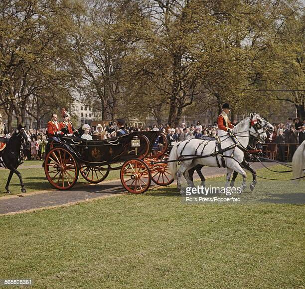 King Faisal of Saudi Arabia rides with Queen Elizabeth II of United Kingdom in a royal carriage through Hyde Park in London during a State visit in...
