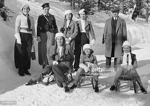 King Farouk of Egypt and his sisters enjoy a holiday in the snow with their sledges