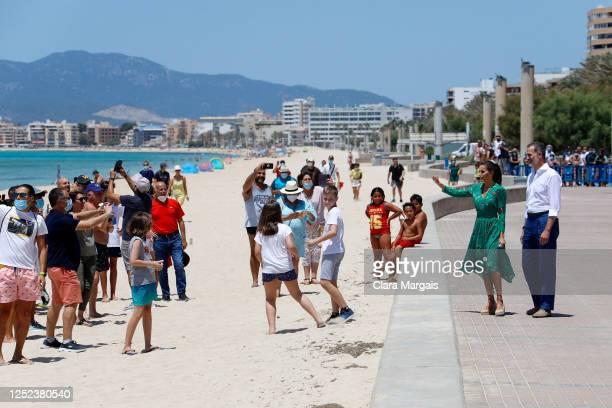 King Felipe of Spain and Queen Letizia of Spain greet spectators as they take a walk on promenade of Platja de s'Arenal on June 25, 2020 in Palma de...