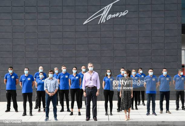 King Felipe of Spain and Queen Letizia of Spain with Fernando Alonso pose with staff members during a visit to the Fernando Alonso Museum and Circuit...