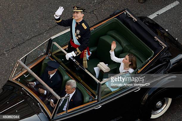 King Felipe VI and Queen Letizia of Spain wave to the crowds during the royal procession down the Gran Via on June 19 2014 in Madrid Spain The...