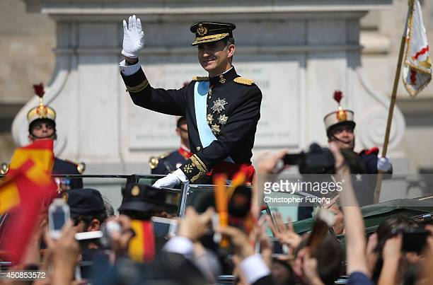 King Felipe VI greets crowds of wellwishers as he arrives at the Royal Palace during the King's official coronation ceremony on June 19 2014 in...