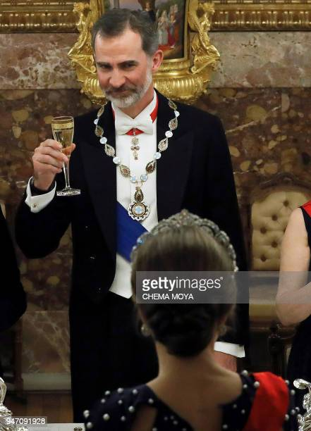 King Felipe VI of Spain and his wife Queen Letizia drink a toast during a state dinner with Portuguese President at the Royal Palace in Madrid on...