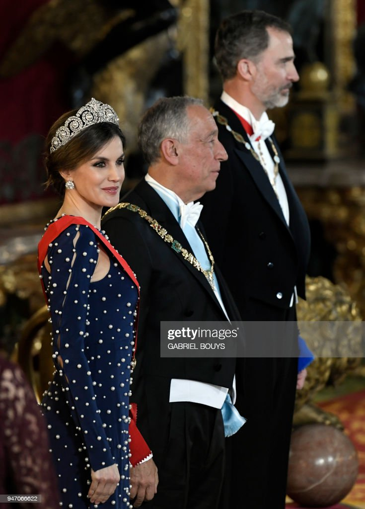 King Felipe VI of Spain (R) and his wife Queen Letizia (L) flank Portuguese President Marcelo Rebelo de Sousa as they receive guests before holding a state dinner at the Royal Palace in Madrid on April 16, 2018. /