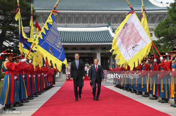 King Felipe VI of Spain and South Korean President Moon Jae-in walk towards a guard of honor during a welcoming ceremony at the presidential Blue...