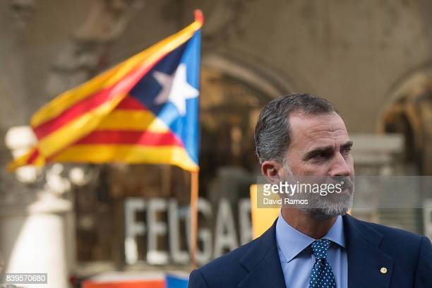 King Felipe VI of Spain arrives to a demonstration against the last week's terrorist attacks next to a Catalonia ProIndependence flag in the...