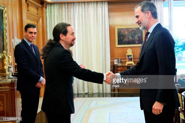 King Felipe VI of Spain greets Spanish Second Vice Minister Pablo Iglesias as Spanish Prime Minister Pedro Sanchez looks on before the start of the...