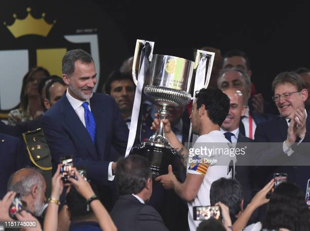 King Felipe VI of Spain hands Dani Parejo of Valencia CF the Copa del Rey trophy at the end of the Spanish Copa del Rey final between Barcelona and...