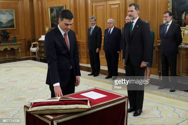 King Felipe VI of Spain looks on as Spain's new Prime Minister Pedro Sanchez takes the oath as President of the Spanish Constitutional Court Juan...