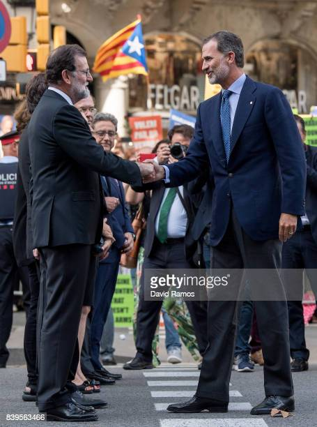 King Felipe VI of Spain shakes hands with Spain's Prime Ministre Mariano Rajoy as they arrive to a demonstration against the last week's terrorist...