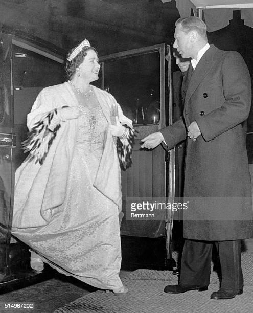 King George graciously assists his Queen Elizabeth from their automobile as they arrive at the London Coliseum to attend a royal command variety...