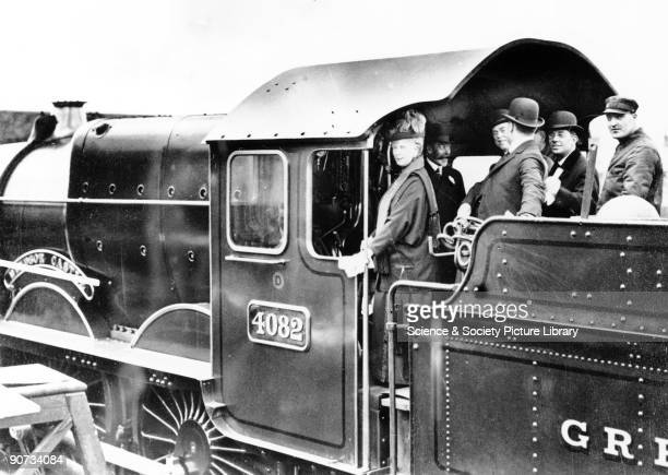 King George tries his hand at driving GWR No 4082 'Windsor Castle' on a visit to Swindon Works. Beside him are Queen Mary, the Chairman of the GWR,...