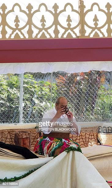 King George Tupou V of Tonga drinks a coconut shell of kava at the pinnacle of the coronation ceremony and taumafa kava ritual in the sacred Pangai...