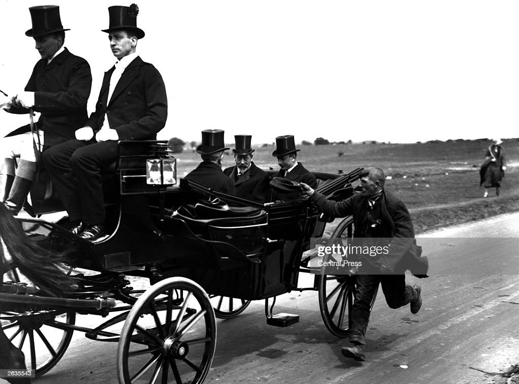 King George V in a horse-drawn carriage at the Epsom Derby, being pursued by a beggar.