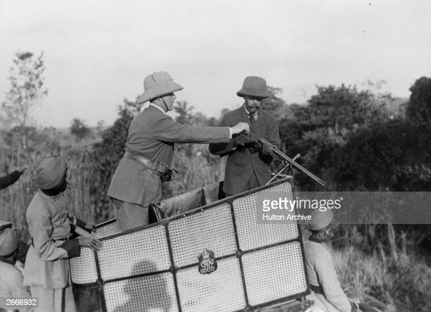 King George V is helped by his loader to load his gun on a tiger hunt in India during his royal visit to celebrate his accession to the throne...